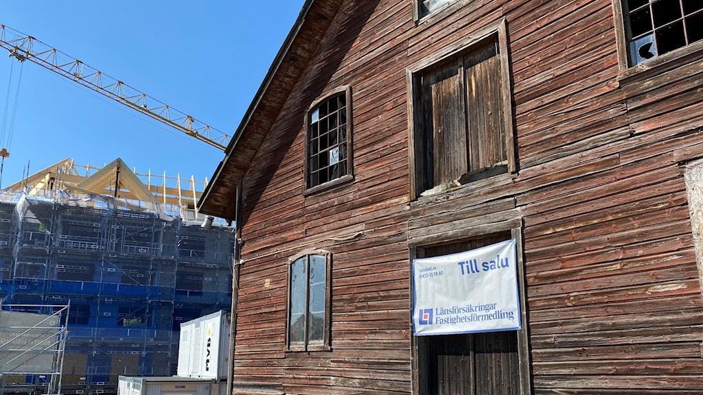 På bilden ser man en del av den rödbruna träbyggnaden Magasinet Kvarnen i Höör. På huset sitter en banderoll från en mäklarfirma om att huset är till salu. Bakom huset skymtar ett bostadsbygge. Foto: Anna Bubenko/Sveriges Radio.