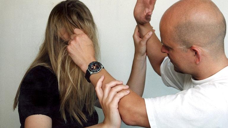 En man drar en kvinna i håret och kvinnan försöker värja sig genom att skjuta mannens händer ifrån sig.  Foto: Claudio Bresciani/TT