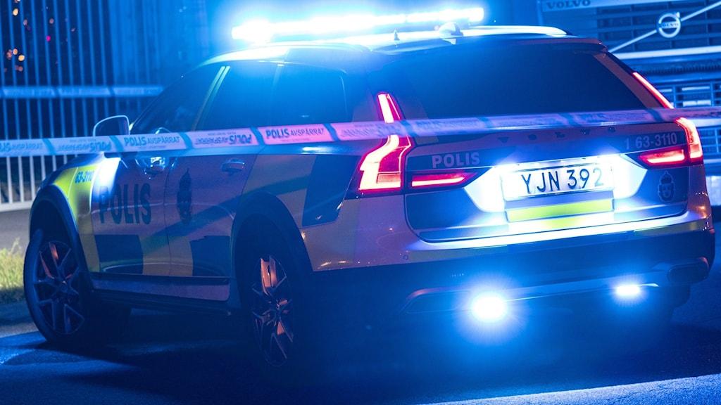 Polisbil med påslagna blåljus i juninatten, parkerad bakompolisen blåvita avspärrningar.