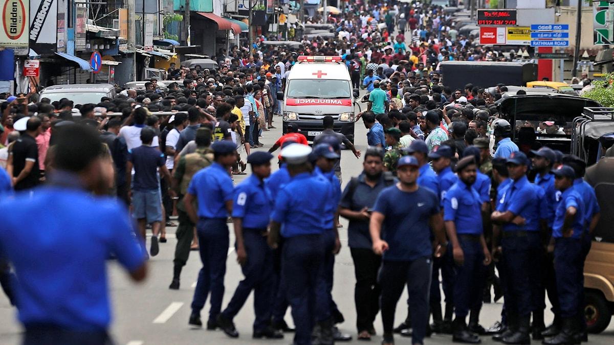 Ambulans som kör längs en gata med folkmassor i Colombo.