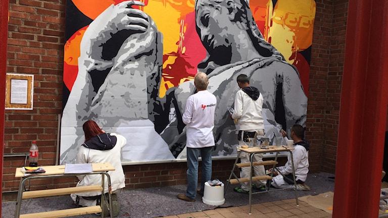 """Deltagare i projektet """"Sätt färg på"""" lägger sista handen vid en stor väggmålning på Drottninghögs centrum"""". Foto: Nina Sköldqvist/Sveriges Radio"""