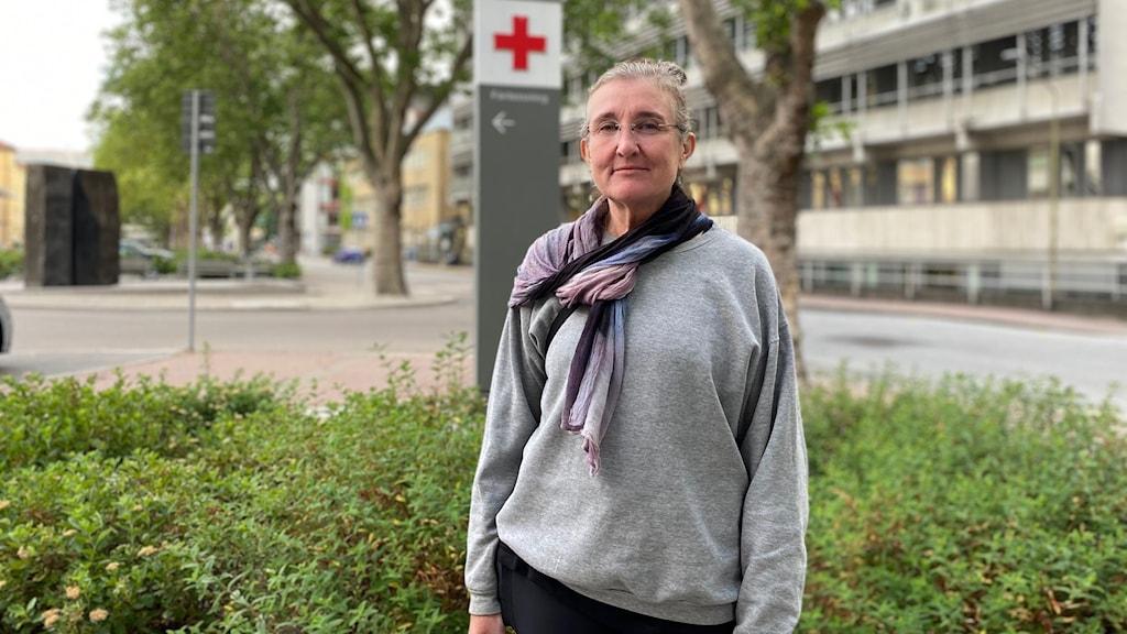 Kvinna utomhus framför sjukhus.
