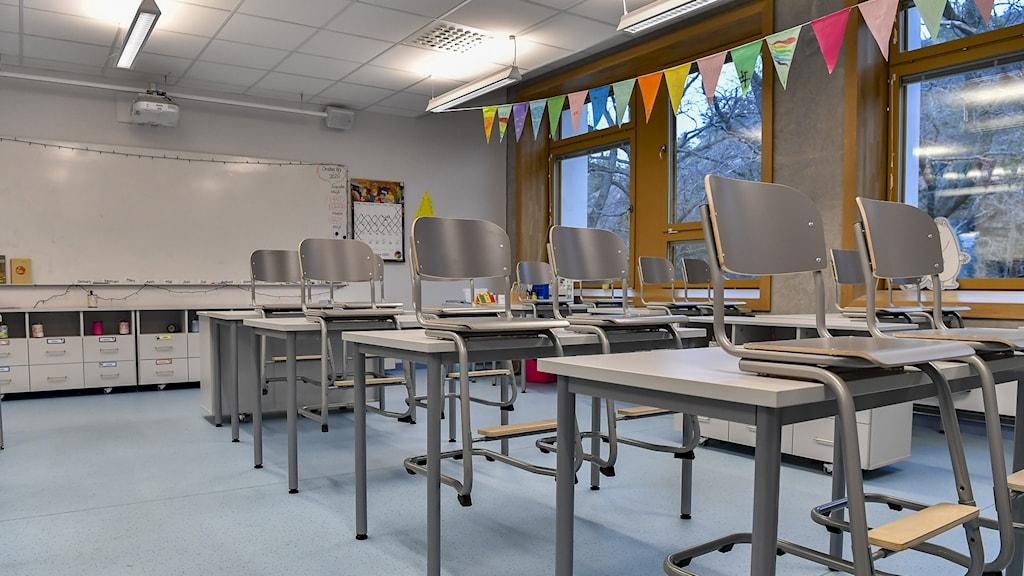 Stolar uppställda på bänkar i ett tomt klassrum.