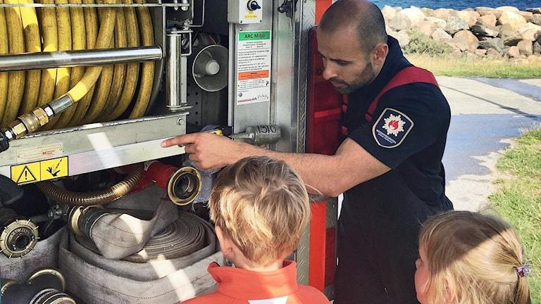 Brandmannen Jihad Fahkrou visar upp brandbilen för sommarlovslediga barn. Foto: Magnus Mosén.