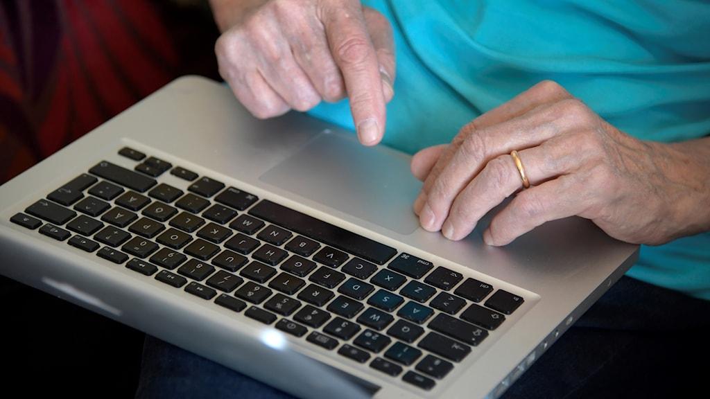 Äldre person som sitter vid en laptop.