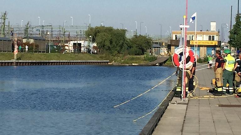 Räddningstjänsten jobbar med bilen som hamnat på taket i kanalen i Malmö.