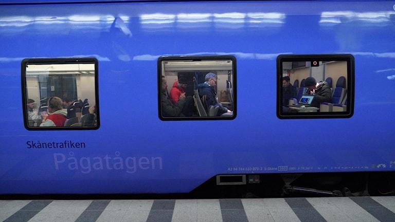 Passagerare på ett stillastående Pågatåg.