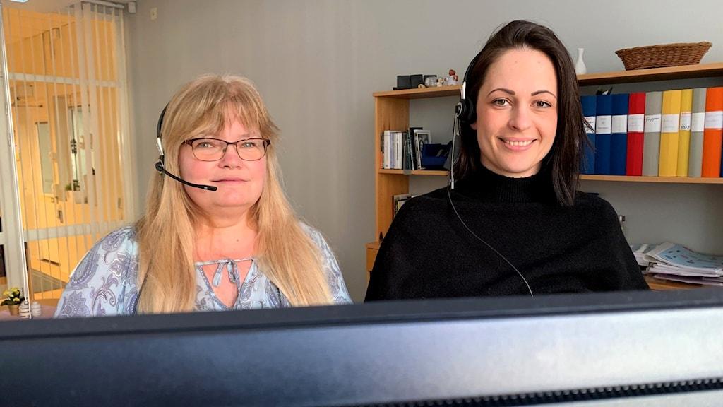 Två kvinnor med headset vid en dator.