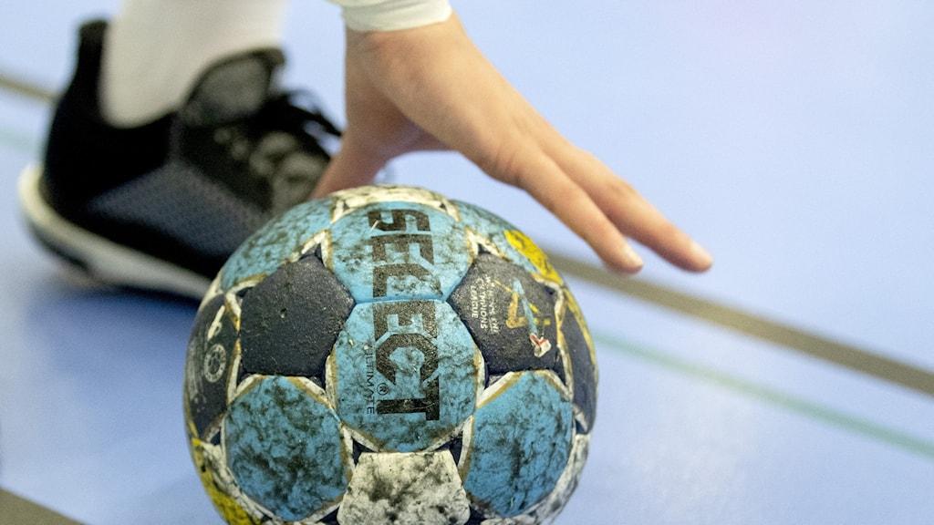 En spelare greppar en handboll