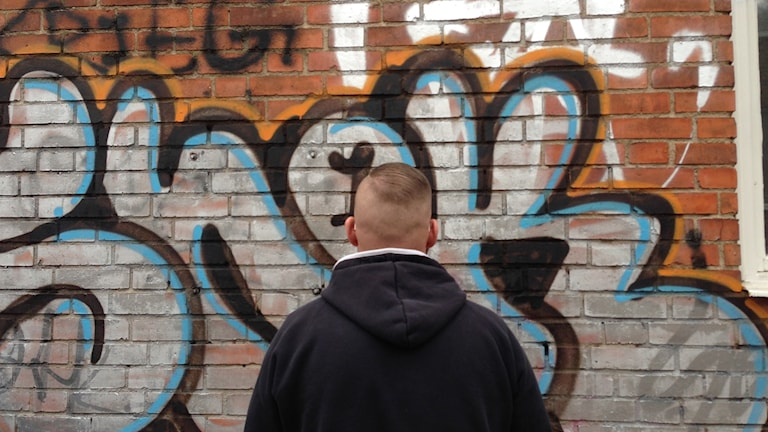 Peter facing a brick wall sprayed with graffiti