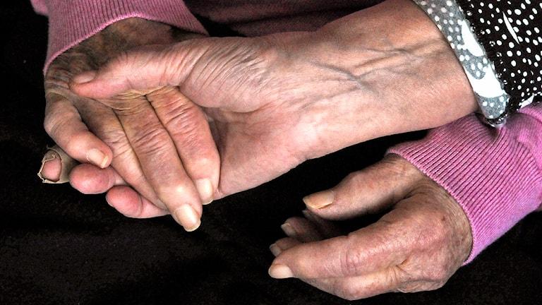 Kvinna håller en äldre kvinnas händer. Foto: Hasse Holmberg/Scanpix