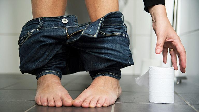 En kvinna sitter på toaletten med neddragna jeans och sträcker sig efter toalettpapper. Foto: Fredrik Sandberg/Scanpix