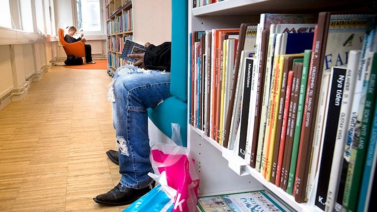 En person sitter och läser böcker på ett bibliotek. Foto: Dan Hansson/TT