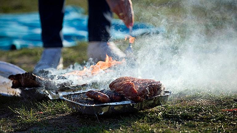En person grillar korv och en köttbit på en engångsgrill med öppen låga. Foto: Fredrik Sandberg/Scanpix