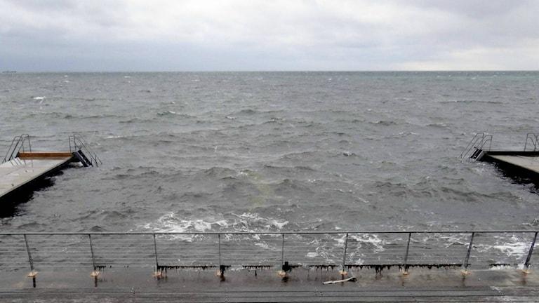 Vågor på havet mellan två bryggor.