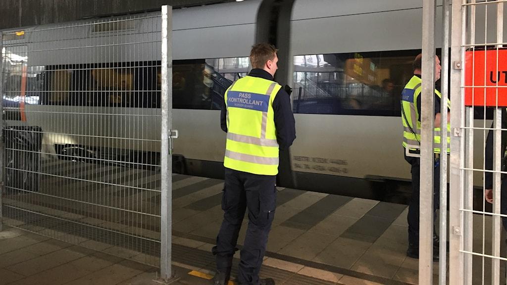 Bilden visar två passkontrollanter, med neonvästar, vid ett Öresundståg som just rullat in på Hyllie station i Malmö. På perrongen finns ett stängsel. Foto: Anna Bubenko/Sveriges Radio.