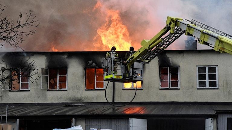 Räddningstjänsten arbetar med att släcka den brand som uppstod i Simrishamns centrum tidigt på torsdagsmorgonen. Foto: Johan Nilsson/TT
