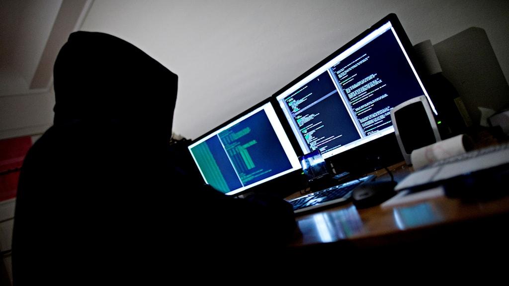 Hackare framför datorskärmar.