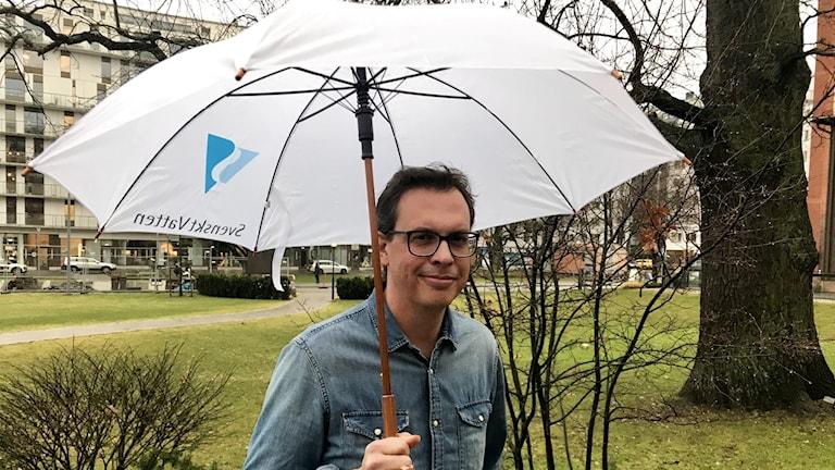 Brunhårig man med glasögon och iklädd jeansskjorta står i en park med ett vitt paraply i ena handen.