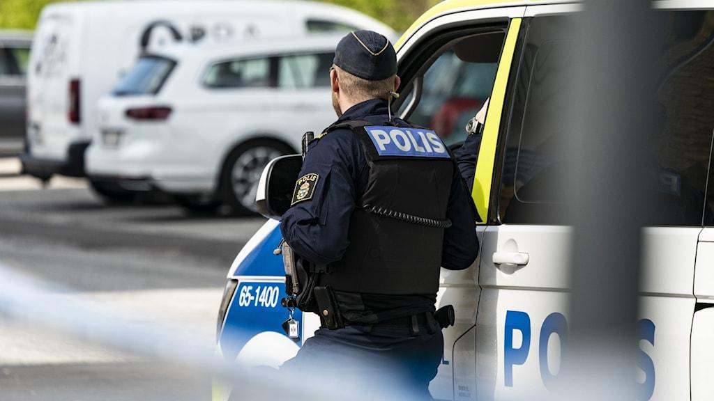 polis med ryggen mot kameran vid avspärrat område