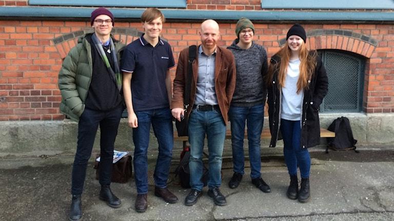 Fem personer står i rad framför en tegelvägg. I mitten står historieläraren Marcus Karlsson med två elever på var sida om honom.