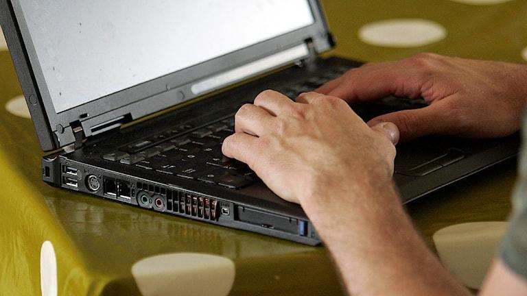 En man sitter hemma och knappar på en bärbar dator. Foto Fredrik Sandberg/TT