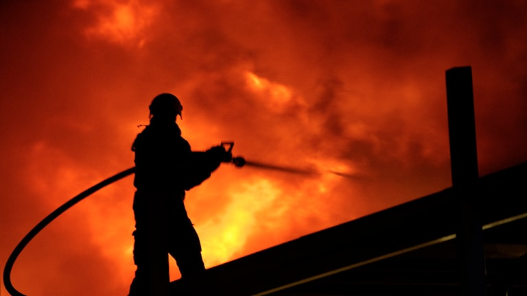 En brandman står på ett tak och släcker en omfattande brand. Foto: Paul Madej / TT