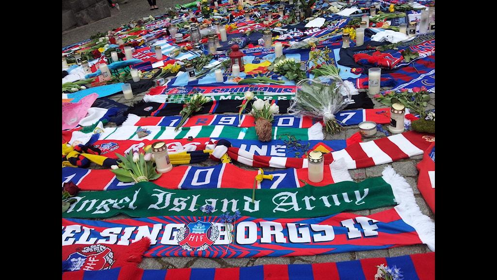 Bilden visar supporterhalsdukar, blommor och ljus som lagts på platsen i Helsingborg där en Djurgårdssupporter misshandlades till döds på söndagen. Foto: Anna Hanspers/Sveriges Radio.