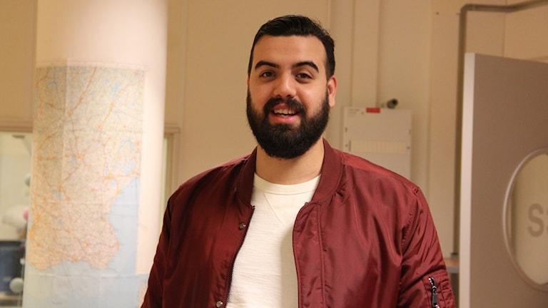 Nadjem Malik har en vit tröja och en vinröd jacka på sig. Han står i studion i Radiohuset i Malmö.