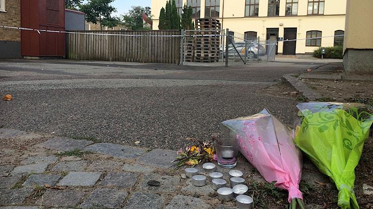 Blommor och ljus har satts ut vid Linnéskolans gård i Limhamn där en 17-åring skars till döds. Foto: Rafaela Stålbalk/Sveriges Radio