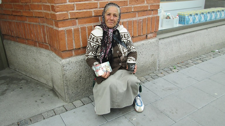 Maria som sitter på trottoaren och sträcker fram en pappmugg. Foto: Raluca Dintica/Sveriges Radio.