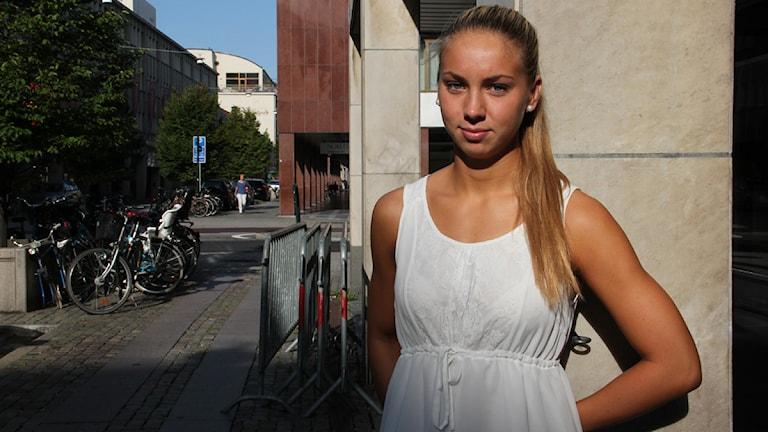 Bilden visar Ellen Olsson lutad mot en pelare utanför radiohuset på Baltzarsgatan i Malmö. Foto: Alexander Zeilon Lund/Sveriges Radio.