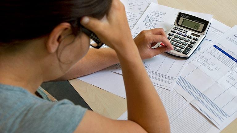 En skuldsatt kvinna sitter lutar över sina räkningar Foto: Claudio Bresciani/TT