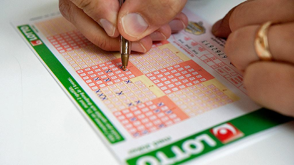En person fyller i en lottorad. Foto: Jessica Gow/TT