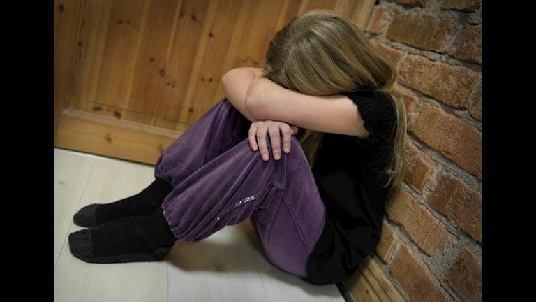 Bilden visar en ledsen flicka som sitter och gråter i ett hörn. Foto: Claudio Bresciani/TT.