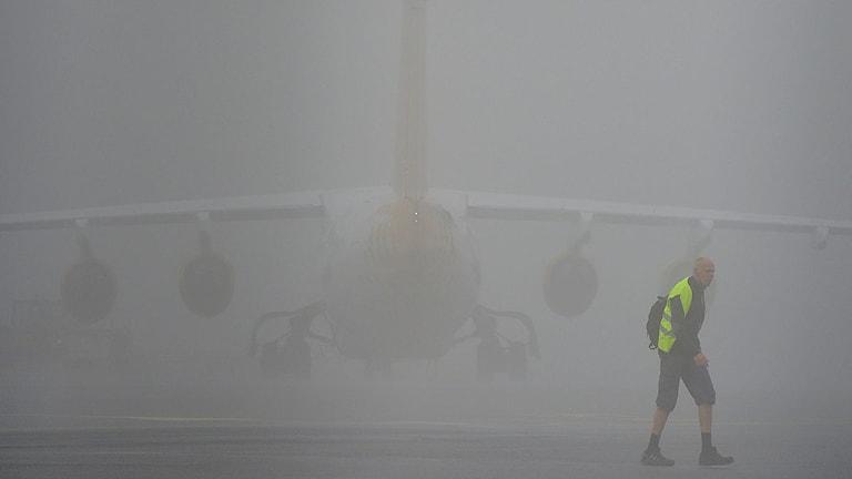 En man med reflexväst framför ett av Malmö Aviations RJ100 flygplan parkerat i dimman på Bromma. Foto: Johan Nilsson/TT