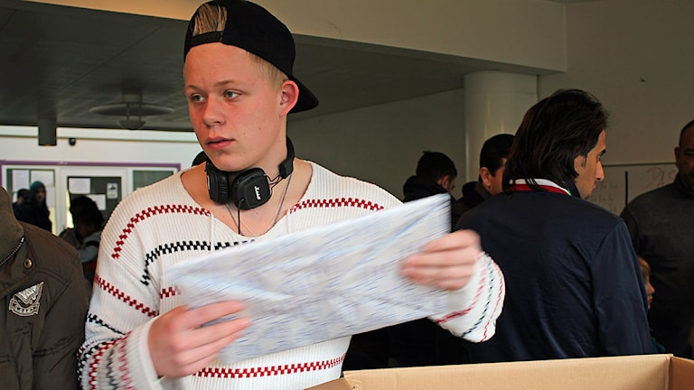 Cornelius Hertzman, en av eleverna på Österlengymnasiet, packar upp julklapparna. Foto: Malin Thelin/Sveriges Radio