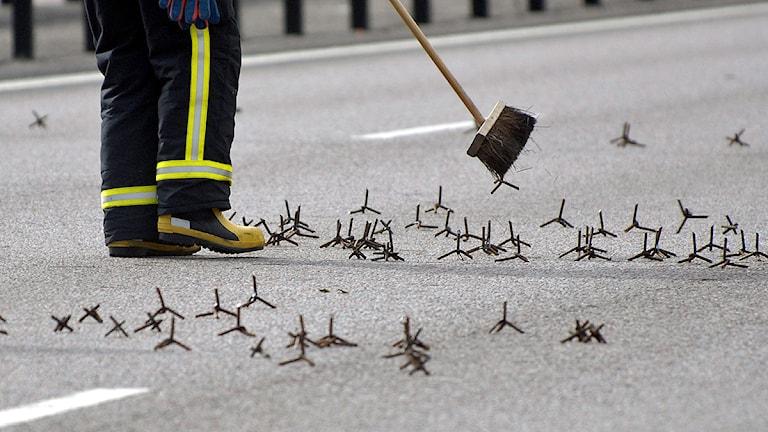 Räddningspersonal sopar undan fotanglar på vägbanan. Foto: Jonas Ekströmmer/TT