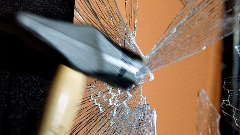 Fönsterruta krossas med hammare. Foto: Claudio Bresciani/TT