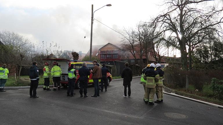 Bilden visar brandmän vid Kvarnby folkhögskola i Malmö,  där rök kommer från taket. Foto: Edina Hrustic/Sveriges Radio.