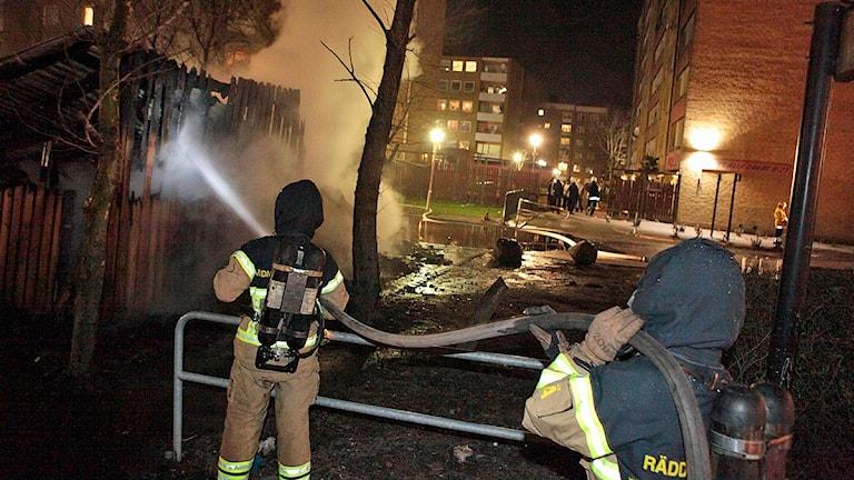 MALMÖ 2009-03-24 Brandmän släcker ett nästan nedbrunnet miljöhus i Malmöförorten Rosengård. Släckningen dröjde eftersom brandmännen blev bombarderade med stenar och flaskor och fick vänta på polisskydd innan de kunde släcka. Foto: Drago Prvulovic/TT