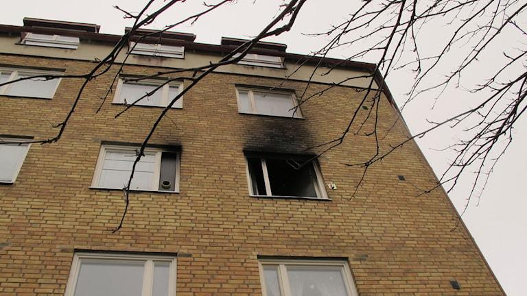 Fönstret på tredje våningen är svart av sot