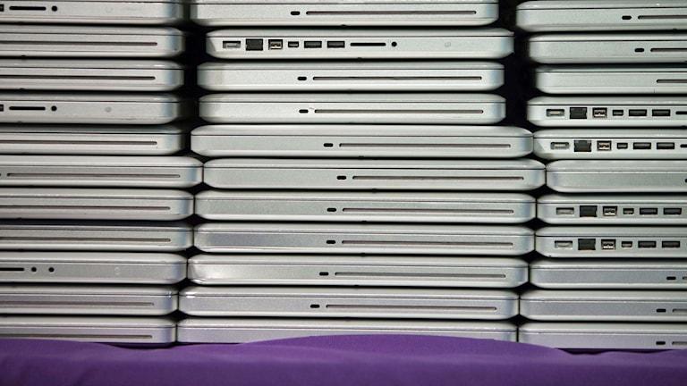 En massa datorer, laptops, staplade på hög. Foto: Alex Washburn/TT.