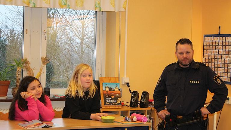 Tredjeklassarna Angeline och Elvira i Hörby fick besök av polisen Joel i kompisprojekt. Foto: Malin Thelin/Sveriges Radio
