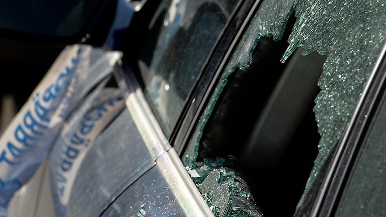 Krossad fönsterruta på bil med polisens avspärrningsband. Foto: Johan Nilsson/TT