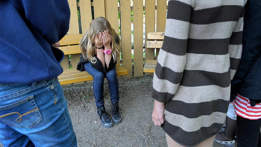 n ensam flicka på en skolgård sitter med händerna för ansiktet medan en grupp flickor tittar på Foto: Janerik Henriksson/TT