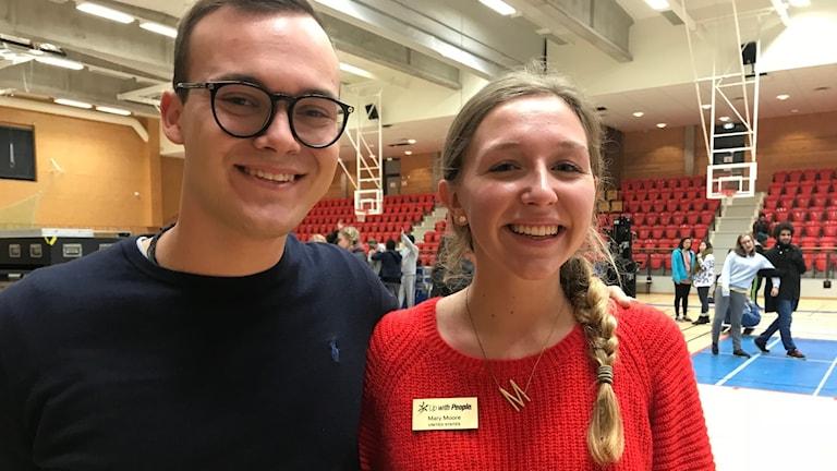 En ung man, André med glas ögon och mörk tröja bredvid en kvinna, Mary Moore, i röd tröja i en idrottshall.