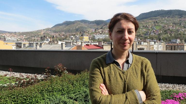 Selma Porobic står med armarna i kors. I bakgunden syns höga gröna kullar. Foto: Svjetlana Pastuhovic/Sveriges Radio.