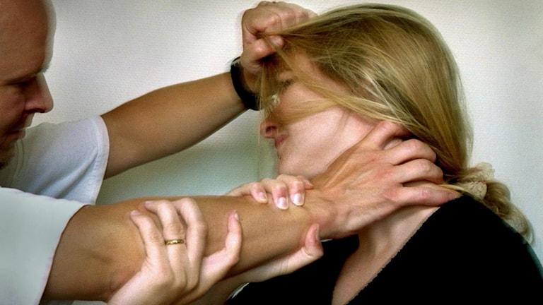 En man drar en kvinna i håret. Foto: Claudio Bresciani/TT