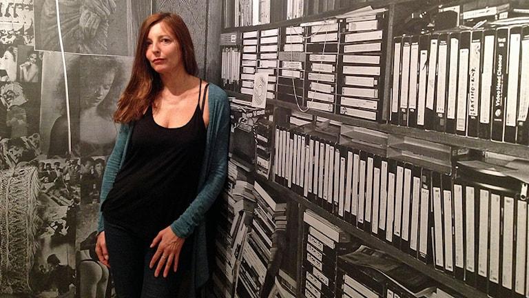 Fotografen Veronique Bourgoin står lutad mot en vägg på fotoutställningen i Landskrona. Foto: David Richter/Sveriges Radio